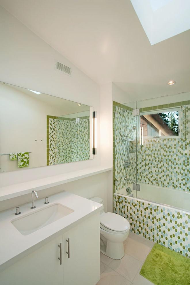 frameless hinged tub door green mosaic wall tile green bathroom mat white vanity white sink mirror toilet window wall sconces