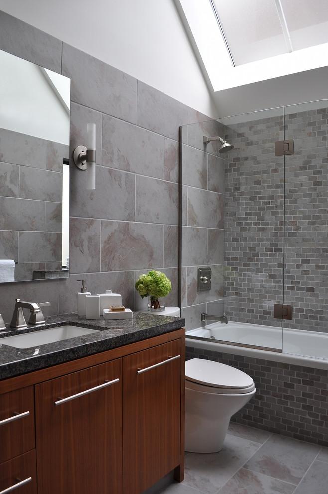 frameless hinged tub door grey wall tile mosaic tile wooden vanity black granite top sink faucet mirror wall sconces shower head tub