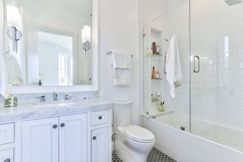frameless hinged tub door wall mirror white vanity white marble top and backsplash built in tub white wall tile black hexagon floor tile