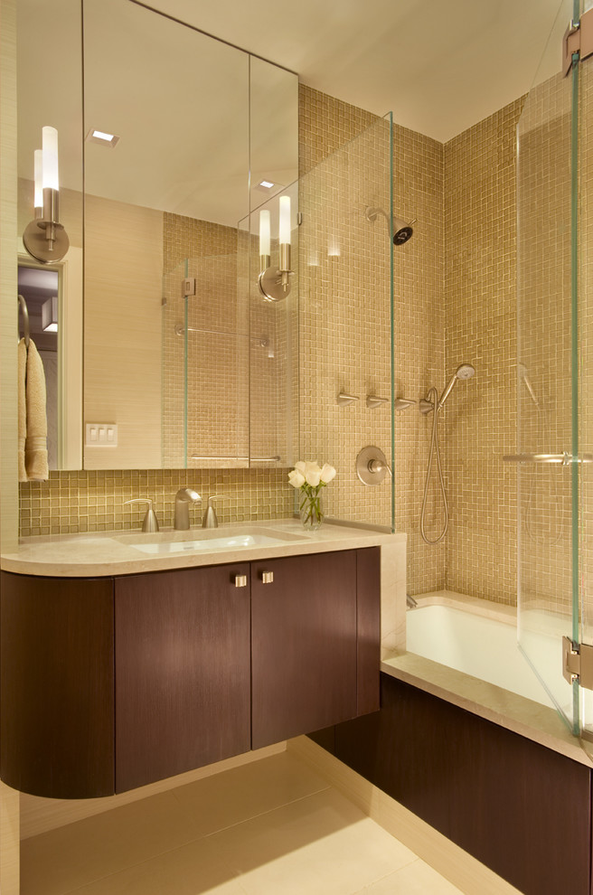 frameless hinged tub door wooden floating vanity beige mosaic wall tile mirrored cabinet wall sconces sink faucet shower head built in tub