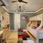 Full Over Queen Bunk Bed Colorful Shag Rug Clock Industrial Chandelier Wooden Desk Wooden Cupboard Shelves Grey Walls Chair