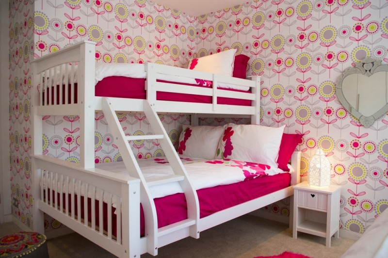 full over queen bunk bed pink and white bedding patterned wallpaper white wooden side table wall mirror table lamp