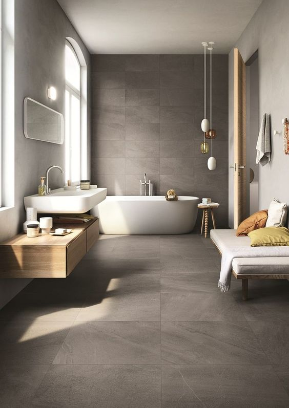 grey bathroom with grey tiles flooring and wall, white tub, white sink with brown cabinet, white bench, white hanging lamp
