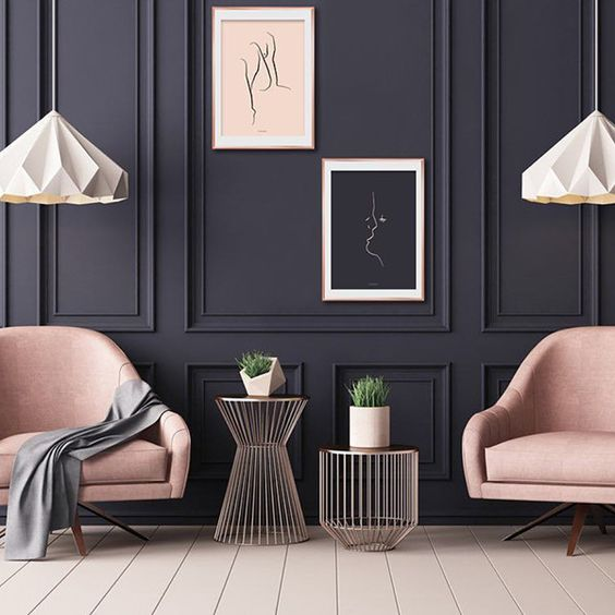 grey living room with dark grey wall, white hanging lamp, pink chairs, gold rose coffee tables