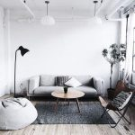 Grey Living Room With White Wall, Grey Sofa, Grey Bean Bag, Wooden Round Coffee Table, Grey Rug, Black Floor Lamp, White Hanging Lamps, Wooden Flooring