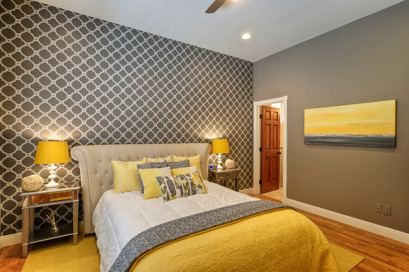 grey yellow bedroom grey patterned wall artwork wooden floor yellow rug beige headboard yellow and grey bedding pillows table lamps mirrored nightstands