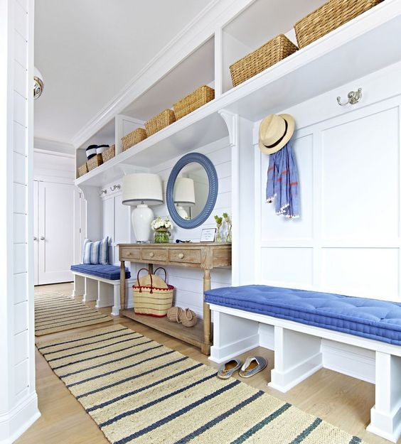 hallways with wooden floor, white bench with blue cushion, white wooden partition with shelves, brown console table, blue framed round mirror, white table lamp