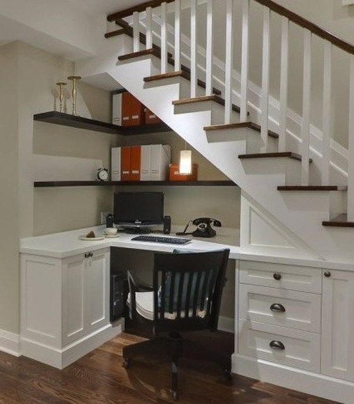home office space under the stairs with white wooden table, brown wooden shelves, brown wooden chairs