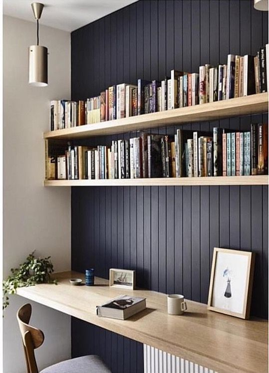 home office with black wooden wall in front, brown wooden table, wooden chair sith cushion, wooden board shelves