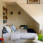 Kids Built In Bed Under A Slanted Space With White Bedding, Storage Under, Bookshelves At The Head Of The Bed