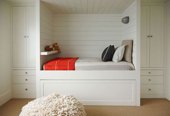 kids built in bed with white wooden bedding, cupboard at the head and foot of the bed, shelves inside