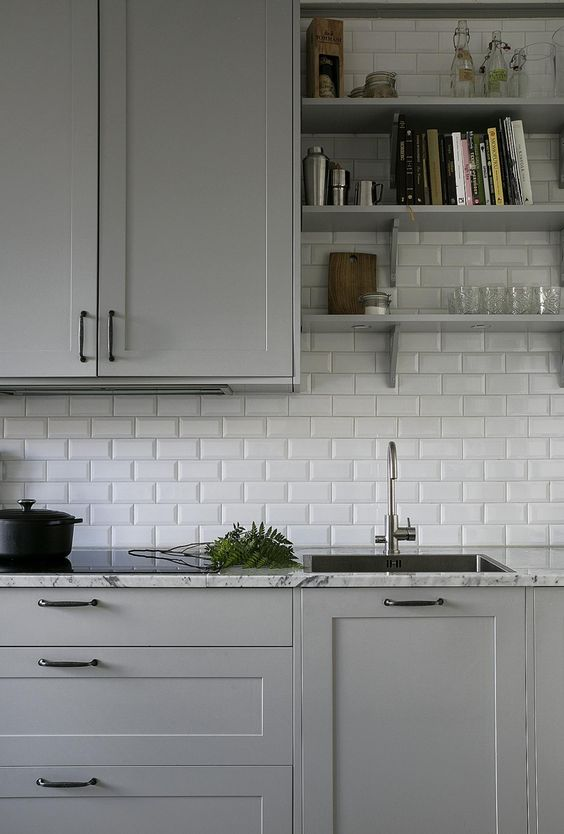 kitchen with grey cabinet, grey marble top, white tiles backsplash, grey cabinet above, grey wooden board shelves