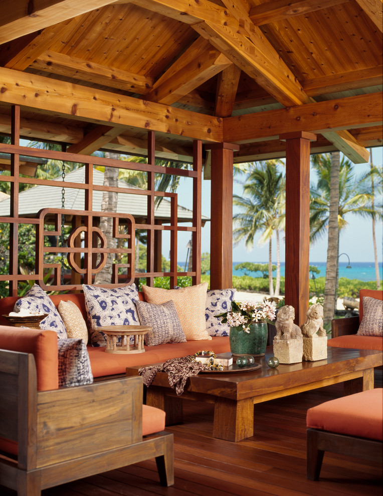lanai with wooden floor, wooden ceiling with wooden beams, wooden chairs and sofas with orange cushions, wooden coffee table, pillows