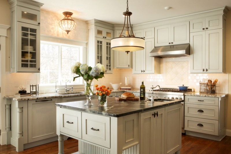 light over kitchen sink grey kitchen cabinets grey island chandelier black marble countertop window stovetop range hood wooden floor