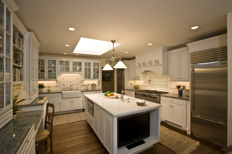 light over kitchen sink kitchen mats white cabinets white island wooden floor stove oven range hood backsplash microwave refrigerator