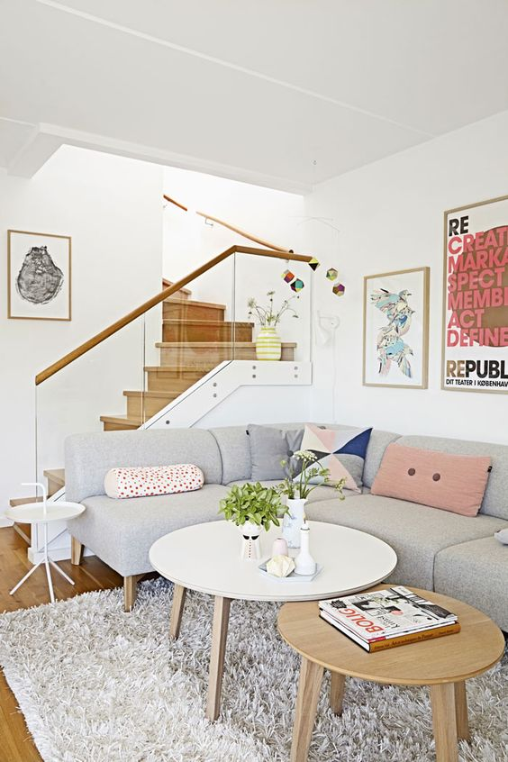 living room near the stairs, with grey corner sofa with soft coloured pillows, white rug, white and brown round coffee tables