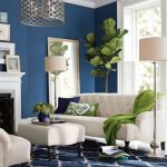 Living Room With Blue Painted Wall, Blue Rug, White Soda, White Ottoman, White Fire Place, White Floor Lamps