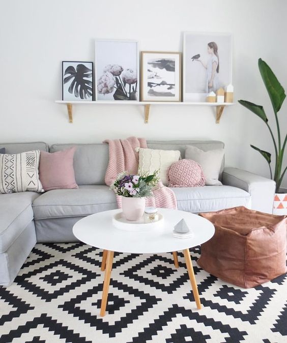 living room with grey corner sofa with pink and grey pillows, white round coffee table, brown leather bean bag, black and white geometrical rug, white hanging shelves