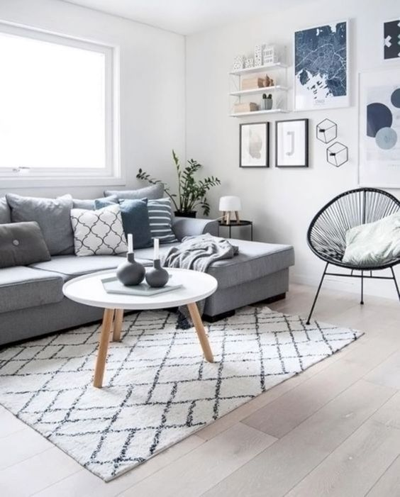 living room with grey sofa, white rug with black lines, black rattan chair, white round coffee table, white wooden shelves, grey pillows