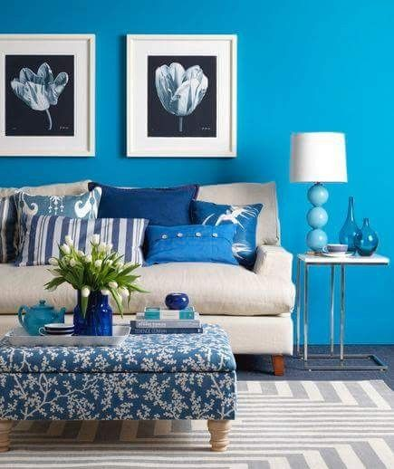 living room with light blue wall, blue pillows and ottoman, white sofa, white side table with metallic feet, white blue table lamp