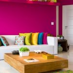 Living Room With Magenta Wall, White Sofa, Colourful Pillows, Wooden Low Coffee Table, White Floor