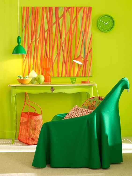 living room with neon yellow wall and table with white marble top, orange painting, orange lamp, orang basket bag, dark green chair, green hanging lamp