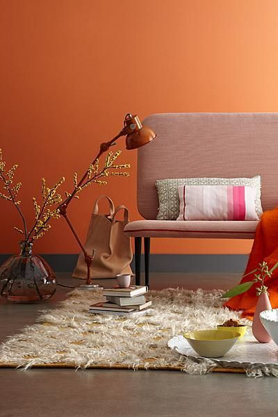 living room with peach wall, peach grey bench, dry plants ornamnent on the floor, white fur rug, pillows, orange blanket