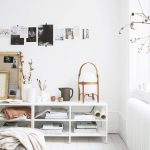 Living Room With White Wall, White Wooden Flooring, White Wooden Low Shelves, White Vases, Soft Coloured Pillows On The Floor