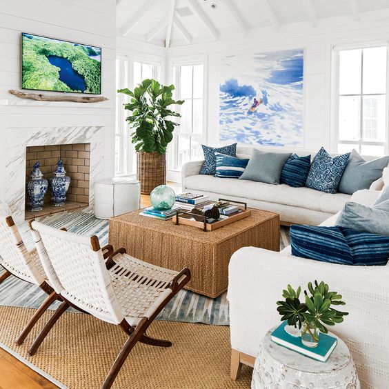 living room with wooden floor, brown rug, white corner sofa, rattan coffee table, white rattan foldable, white wooden wall, white marble fireplace, plants with rattan vase