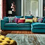 Living Room With Wooden Floor, Grey Rug, Green Sofa, Green Wall, White Door, Yellow Ottoman