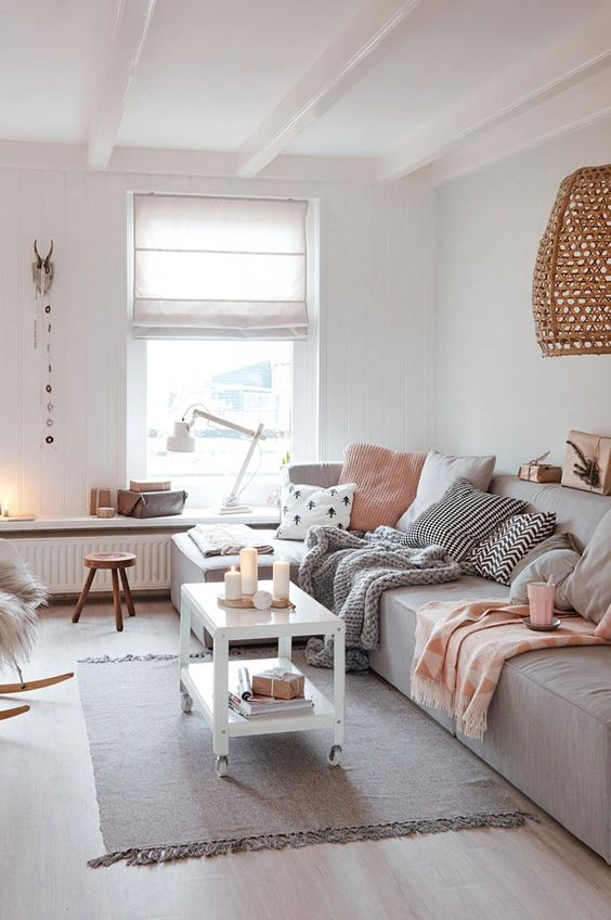 living room, with wooden flooring, grey sofa, white wooden coffee table, white long table with brown wooden stools, rattan hanging lamp