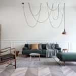 Living Room With Zigzag Wooden Flooring, Grey Rug, Deep Green Sofa And Ottoman, Dark Brown Chair, Light Brown Wooden Shelves, Pendant With Dramatic Cable