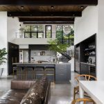 Open Space With Grey Floor, Brown Leather Sofa, White Wooden Table With Brown Wooden Chairs, Grey Island With Grey Marble Top, Golden Metallic Stools With Black Cushion