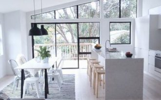 open space with wooden floor, white island with wooden stool, white dining set with striped rug, grey sofa, orang ottoman