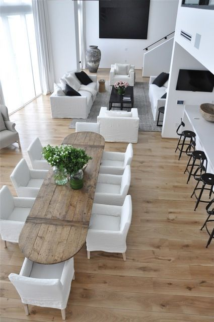 open space with wooden floor, white wall, wooden dining table with white chairs, living area with white sofas, black coffee table, grey rug, white islan, black metal stool