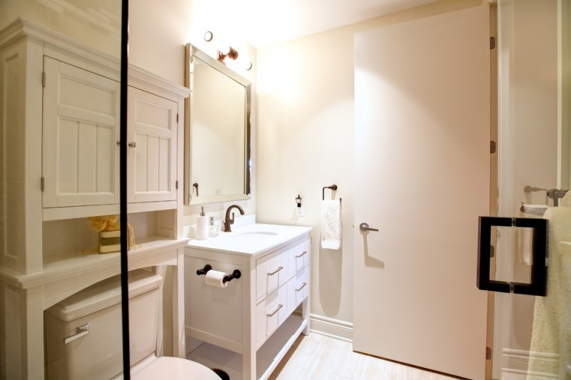 over the toilet storage wooden storage white vanity sink faucet wall sconce wall mirror glass shower door towel holder