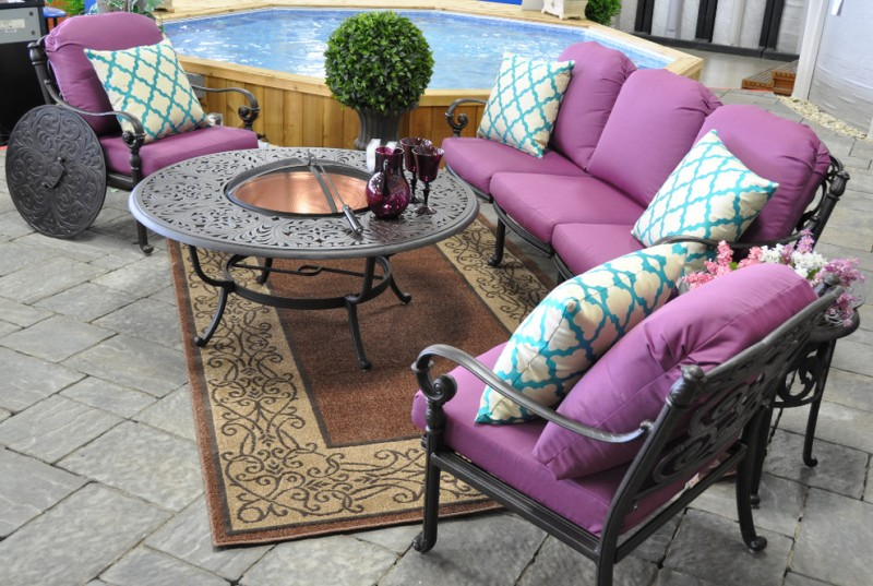 patio with concrete flooring, brown rug, metal chairs with purple cushions, white blue pillows, metal coffee table