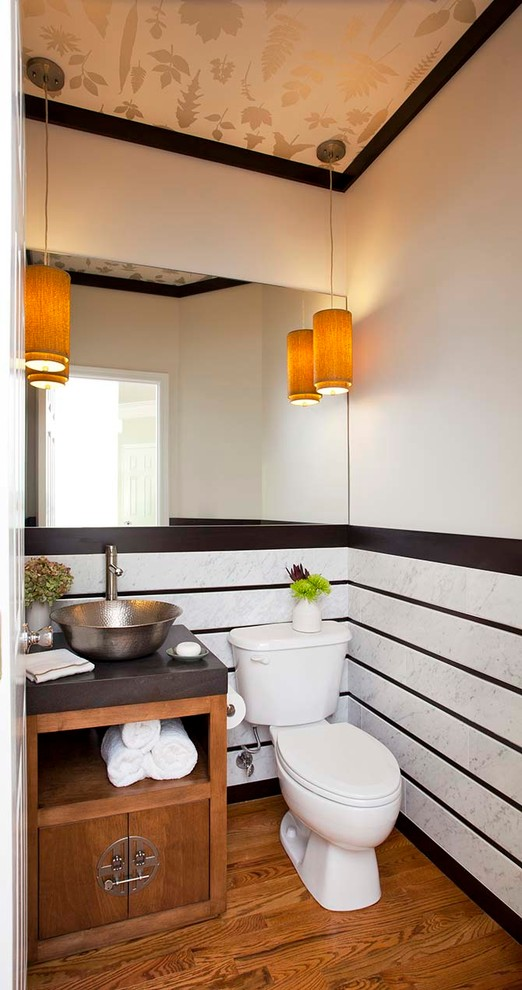 powder room with wooden floor, white toilet, white striped wall, brown wooden cabinet with dark brown top under metallic sink
