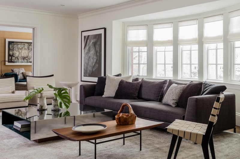 rustic modern coffee table mirrored coffee table grey sofa grey and white throw pillows white windows chair white striped armchairs area rug artwork