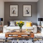 Rustic Modern Coffee Table Wheeled Table Yellow Chair Colorful Area Rug Black And White Artworks White Sofa Throw Pillows Grey Walls Side Tables Grey Curtains