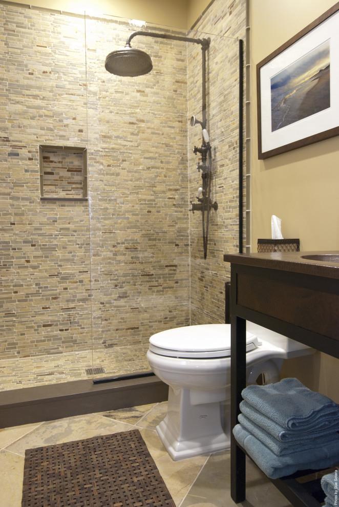 sliding shower head mosaic wall tile toilet wooden vanity undermount sink bathroom mat blue towels glass shower door artwork beige walls
