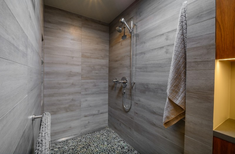 sliding shower head towel holder grey wall tiles wooden cabinet recessed lighting towel holder mosaic floor tile