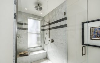 sliding shower head white marble wall tile black mosaic tile rainfall shower glass shower door built in bench frosted glass windows artwork