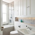 Small Bathroom With Light Brown Wooden Floor, White Upper Cabinet, White Sink, White Toilet, White Tub Covered With Grey Tiles To The Wall, Ornamented Tiles Backsplash