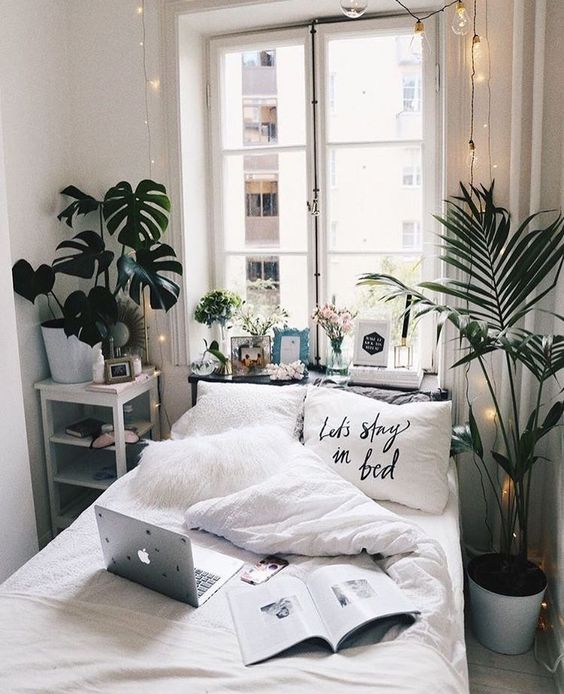 small bedroom with light grey wooden floor, white bed and pillows, plants, white shelves beside the bed, windows