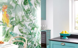 small kitchen wih blue cabinet with black top, small square table with wooden rattan chairs, tropical leaves wallpaper