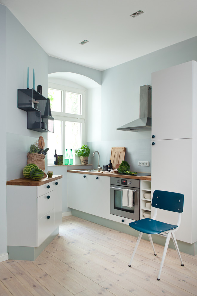 small kitchen with white cabinet with wooden top, light grey painted wall, black metallic racks upper, white fridge, blue chair, white wooden floor