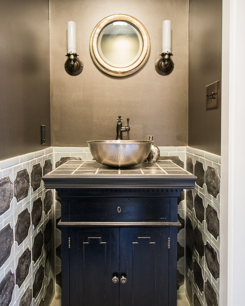 small powder room with blue wooden cabinet under round metallic basin sink, metallic round framed mirror