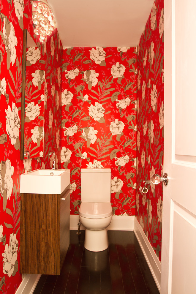 small toilet with dark brown wooden floor, white toilet, dark brown floating cabinet with white marble sink on top, mirror, red wallpaper with white flowers