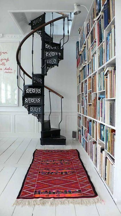 spiral stairscase with black metal material, wooden handrail supported with black metal fence